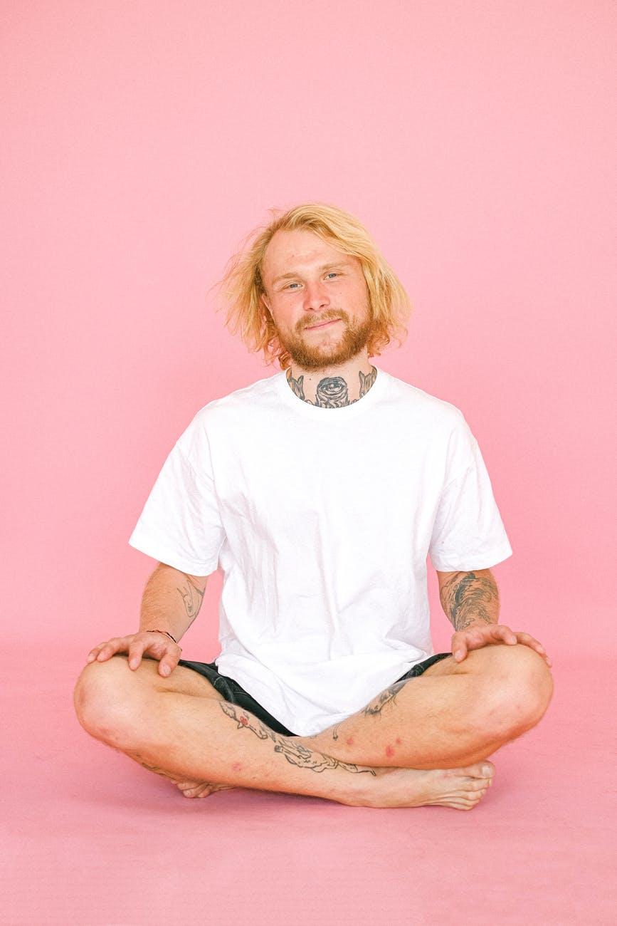 calm man meditating on pink background